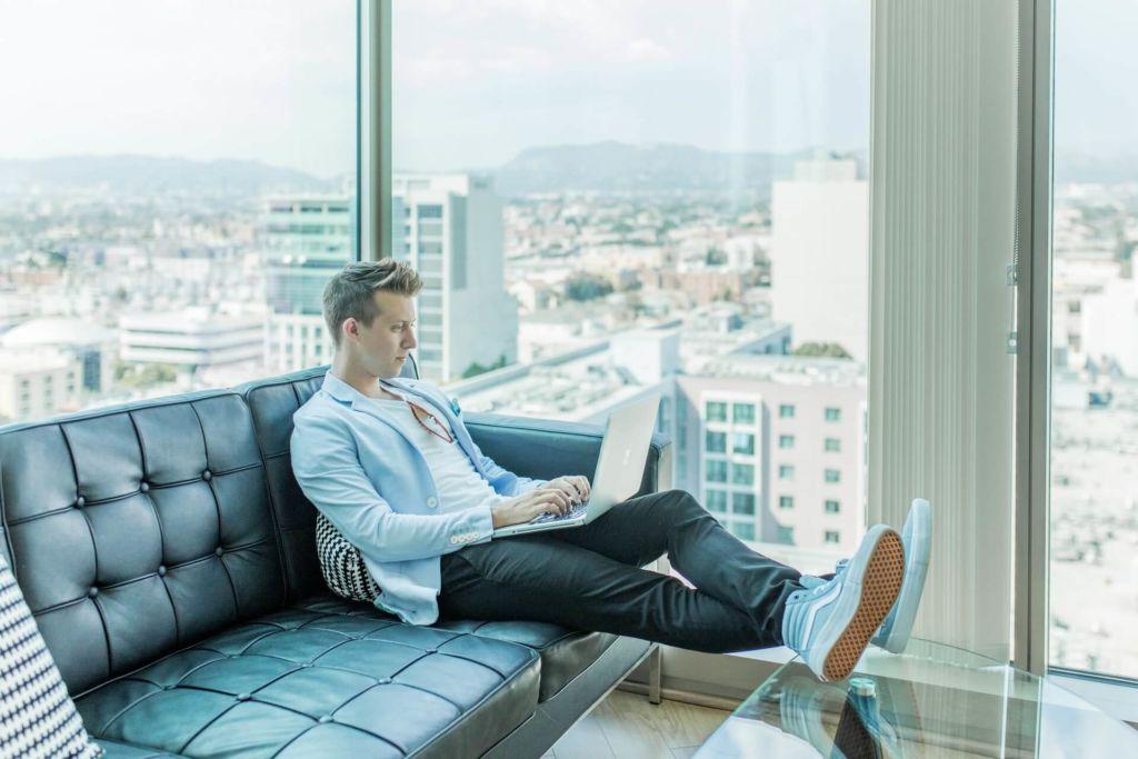 mężczyzna siedzący na kanapie laptopem na kolanach