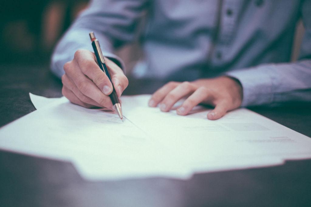 zbliżenie na dłoń z piórem, która pisze na kartce